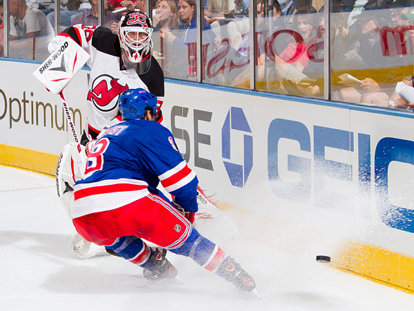Devils goalie Martin Brodeur clears the puck past the Rangers' Brandon Prust