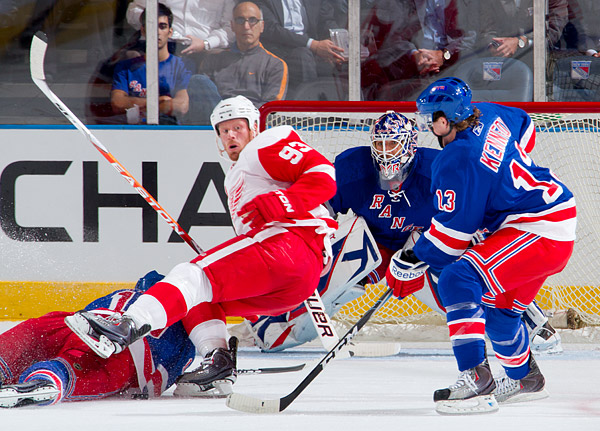 Red Wings forward Johan Franzen gets tripped up in the offensive zone while Rangers goalie Henrik Lundqvist and forward Tim Kennedy look on
