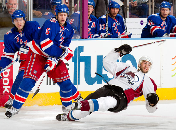 Dan Girardi (#5) of the Rangers sends an Avalanche player down to the ice