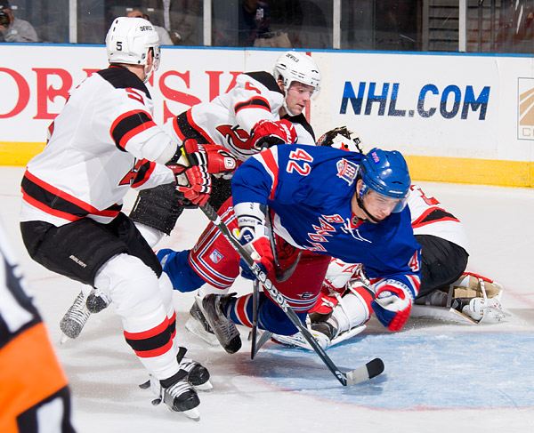 The Rangers' Artem Anisimov gets pushed from behind while rushing the net