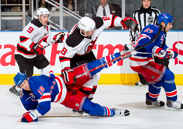 New York's Marc Staal goes down while teammate Michal Rozsival and New Jersey's Zach Parise and Dainius Zubrus chase the puck