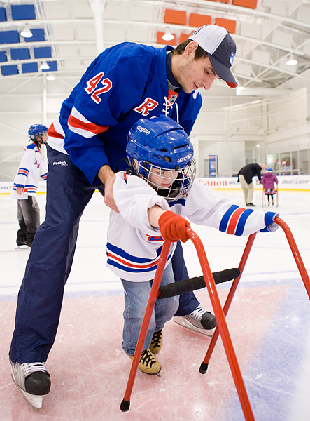 A young boy gets skating lessons from Rangers player Artem Anisimov