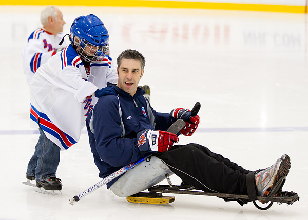A child offers his assistance to a Rangers sled hockey player