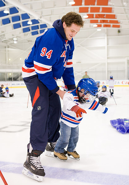 A young boy gets skating lessons from Rangers player Derek Boogaard