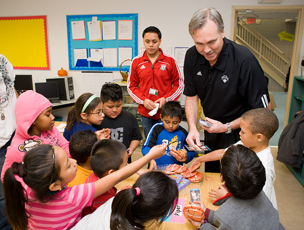 Head coach Mike D'Antoni hands out cookies and bookmarks in a classroom