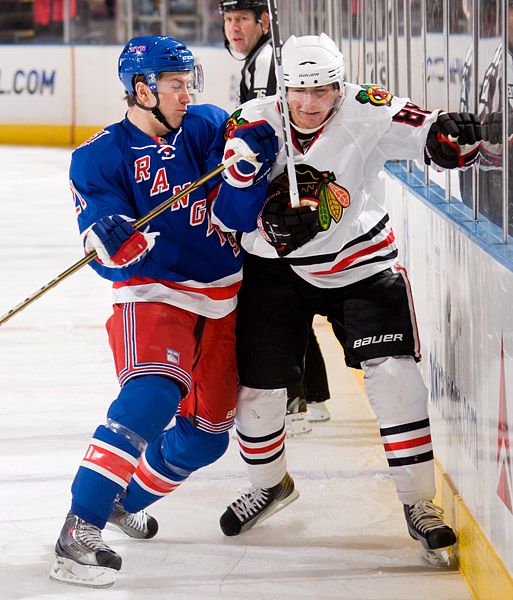 Ranger Derek Stepan checks the Blackhawk Patrick Kane