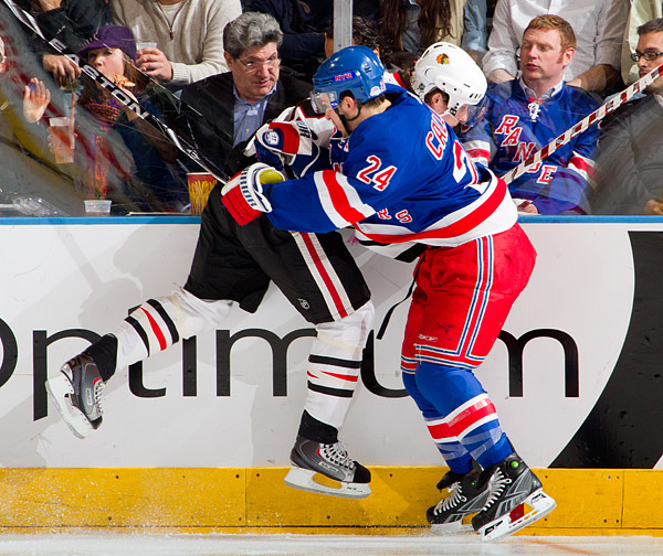 New York's Ryan Callahan checks a Chicago player into the boards