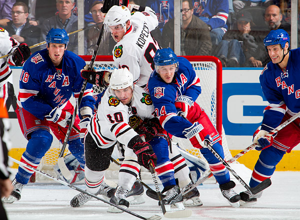 New York's Ryan Callahan (#24) bats the puck away from Chicago's Patrick Sharp and Tomas Kopecky