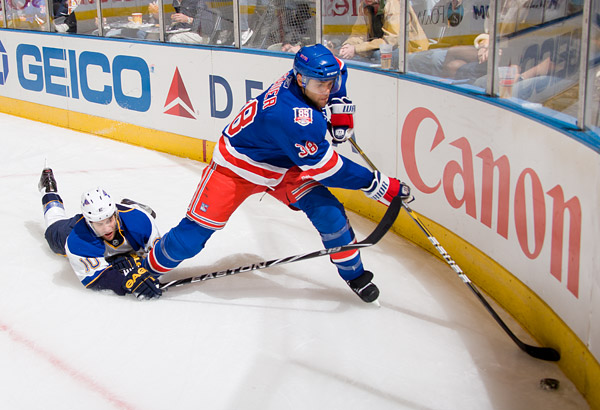New York's Michael Sauer keeps the puck away from St. Louis's Andy McDonald
