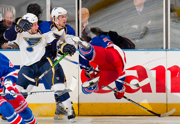 The Blues send the Rangers' Michal Rozsival flying into the boards