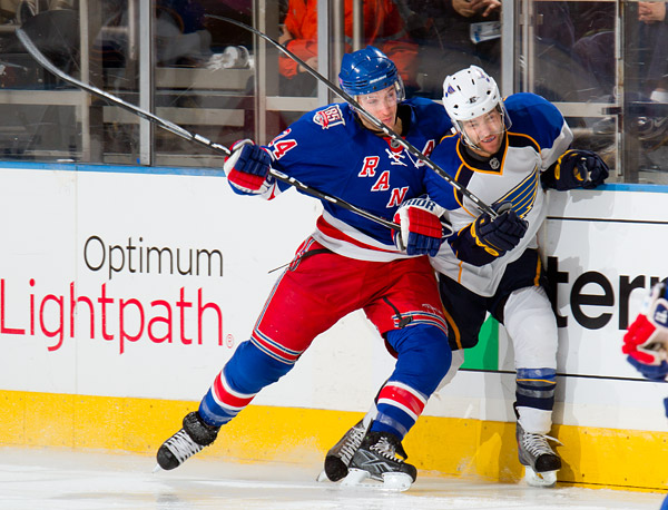 The Rangers' Ryan Callahan checks a Blues player into the boards