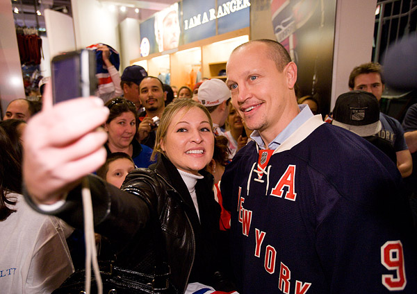 A fan takes her own photo with Rangers legend Adam Graves, who helped the team win the Stanley Cup in 1994