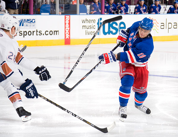 New York's Marian Gaborik shoots the puck, knocking an opponent's stick away in the process