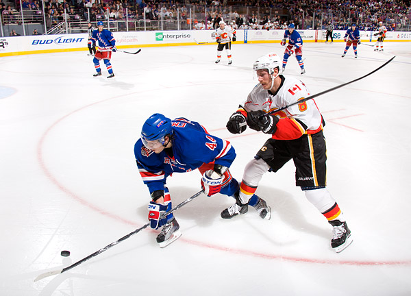 Rangers defenseman Steven Eminger plays keep-away with the Flames' Brendan Morrison