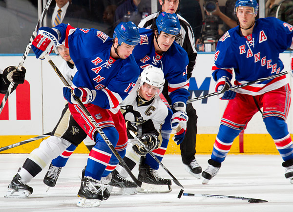 New York's Brandon Dubinsky (#17) battles for the puck with Pittsburgh's Sidney Crosby
