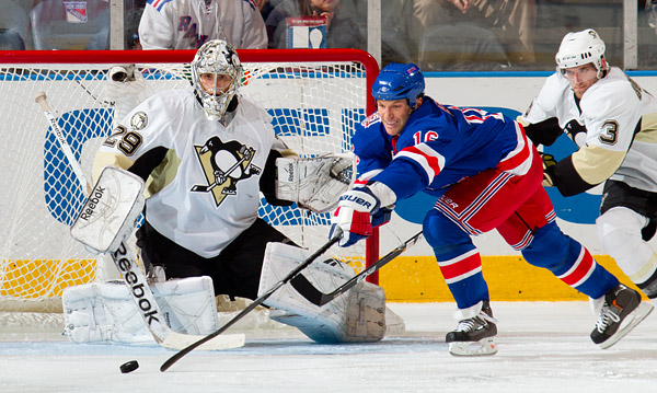 The Rangers' Sean Avery reaches to shoot the puck against Penguins goalie Marc-Andre Fleury