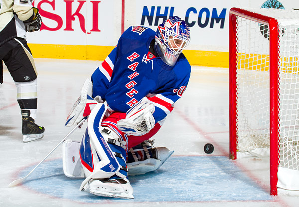 Rangers goalie Henrik Lundqvist looks back at a puck that narrowly misses the net