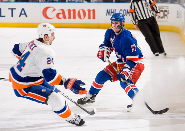 The Rangers' Brandon Dubinsky clears the puck past the Islanders' Radek Martinek