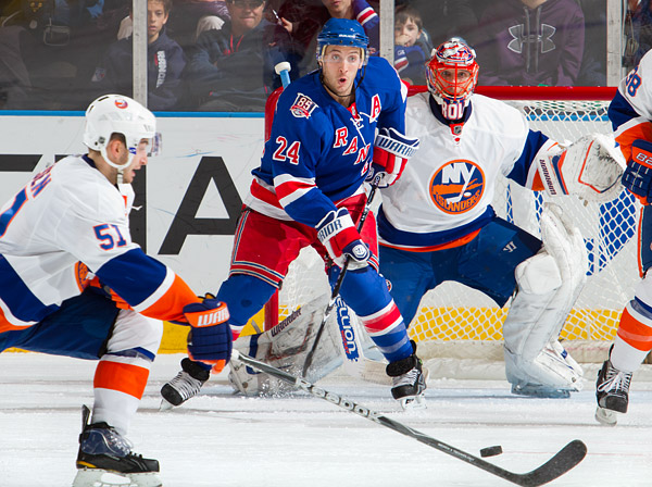Ryan Callahan of the Rangers looks to deflect a shot past Islanders goalie Dwayne Roloson as Frans Nielsen (#51) attempts to block it