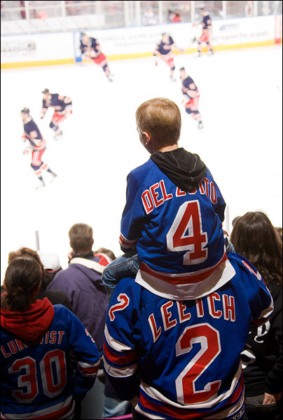 A supporter of Michael Del Zotto, one of this decade's promising young defensemen, sits atop the shoulders of a fan of Brian Leetch, the Rangers' Hall of Fame defenseman from the 90's, during pregame warmups