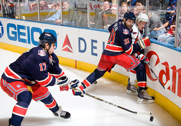 New York's Brandon Dubinsky handles the puck while teammate Alex Frolov pins a Washington player against the boards