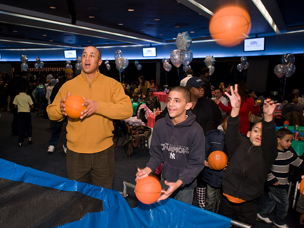 Retired New York Knicks star John Starks shoots hoops with a couple of the kids