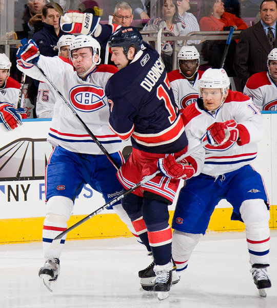 The Rangers' Brandon Dubinsky skates between two Canadiens