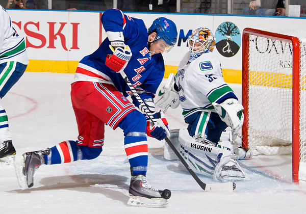 New York's Artem Anisimov attempts to knock a puck past Vancouver goalie Cory Schneider