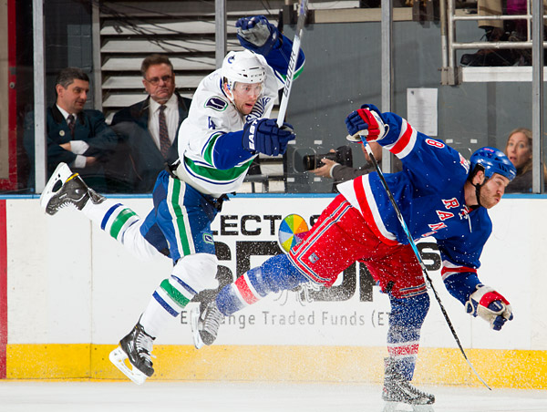 Vancouver defenseman Keith Ballard gets some airtime courtesy of New York's Brandon Prust