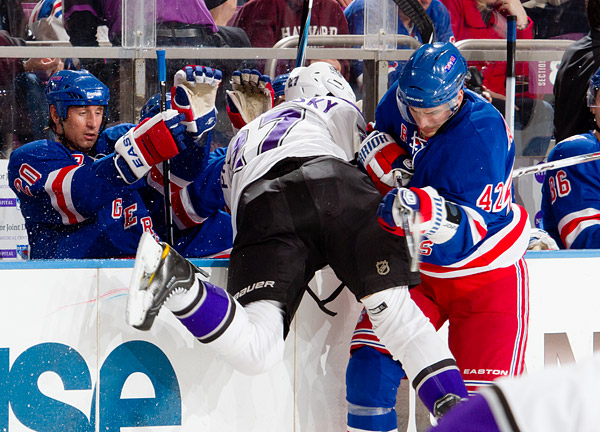 New York's Artem Anisimov sends Los Angeles's Alexei Ponikarovsky into the Rangers' bench
