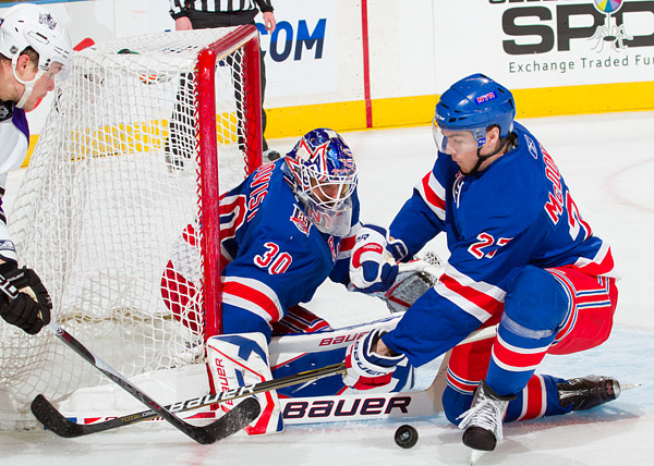 Henrik Lundqvist stops a shot with the help of defenseman Ryan McDonagh