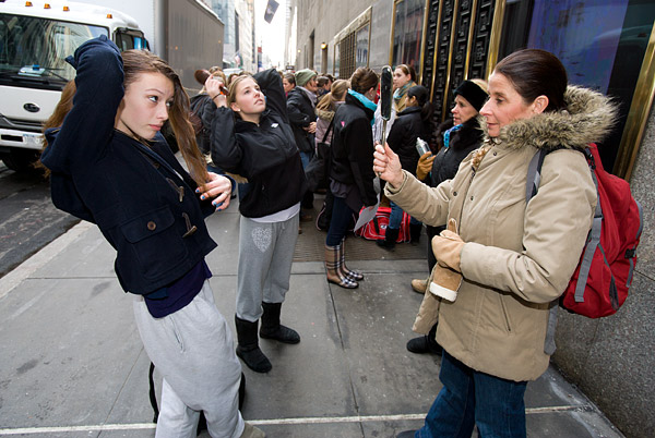 Dancers and their moms work on some last minute hair touchups while waiting outside before the audition