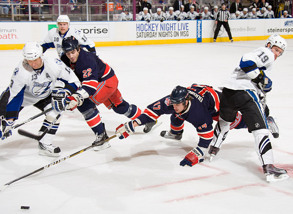 The Rangers' Brandon Dubinsky lunges for the puck after a faceoff with the Lightning's Dominic Moore (#19)