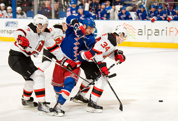 New York's Marian Gaborik tries to squeeze between two Devils in pursuit of the puck