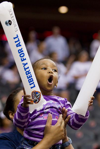 A young Liberty fan cheers on her team