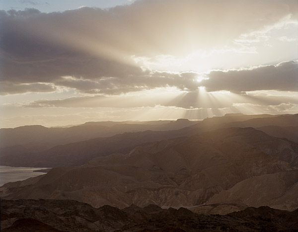 The sun streaks through the clouds over the Eilat Mountains by the Red Sea