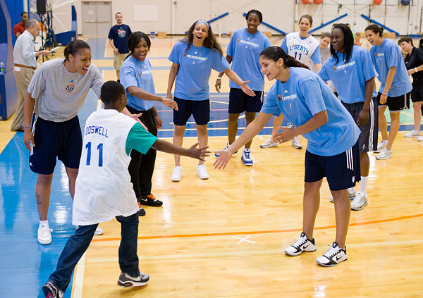 Kids get introduced in the Madison Square Garden Training Center gym with a New York Liberty basketball high-five line