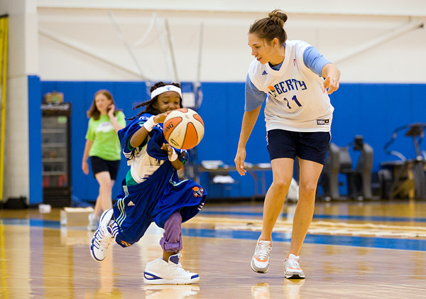Liberty player Sidney Spencer helps out with a dress and dribble game