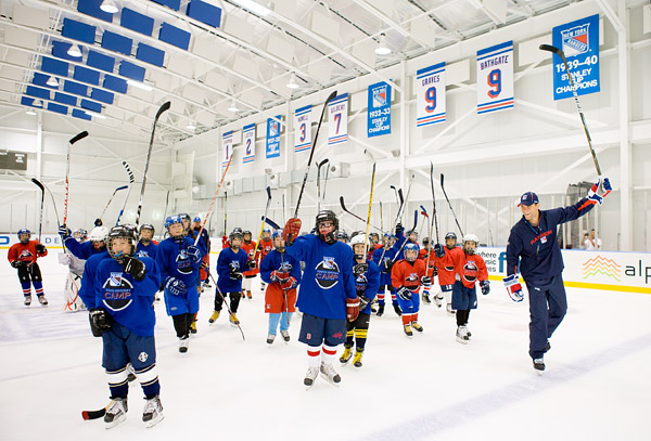 Michael Sauer leads a hockey camp stick salute