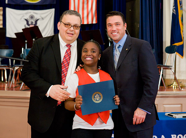 The school principal and Congressman Grimm present an award to a student