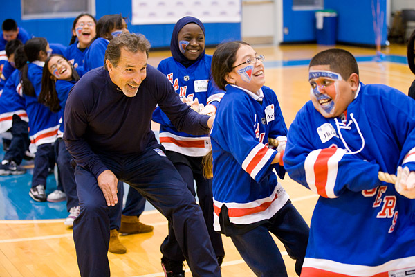 New York Rangers head coach John Tortorella helps his teammates in tug-of-war at the Garden of Dreams Foundation's Coaches Challenge