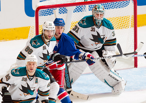 New York's Brandon Dubinsky, who had two assists in the game, looks to make a play in front of the net, surrounded by San Jose's Ryane Clowe (#29), Brent Burns (#88) and goalie Antti Niemi
