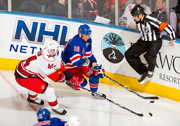A referee jumps out of the way of New York's Marian Gaborik and Carolina's Jay Harrison