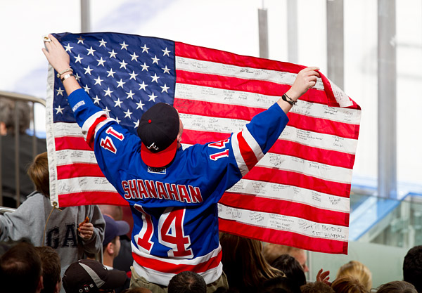 A fan holds up an American flag in honor of Veterans Day