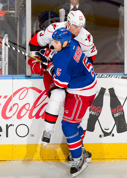New York's Dan Girardi checks Carolina's Alexei Ponikarovsky into the boards
