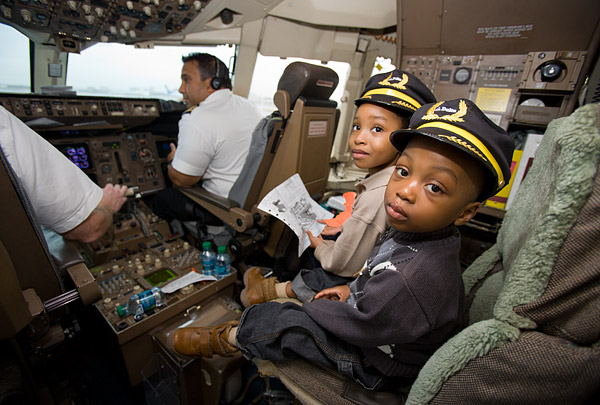A pair of Junior Pilots help fly a plane full of kids to the North Pole for the Garden of Dreams Holiday in the Hangar party.