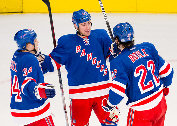 New York Ranger Brandon Dubinsky celebrates with teammates John Mitchell and Brian Boyle after scoring in the first period.