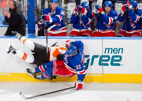 Anton Stralman checks Philadelphia Flyer Matt Read into the boards in front of the New York Rangers bench