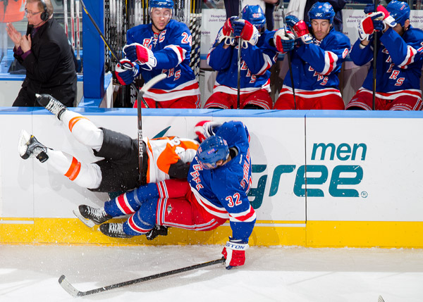 Anton Stralman checks Philadelphia Flyer Matt Read into the boards in front of the New York Rangers bench