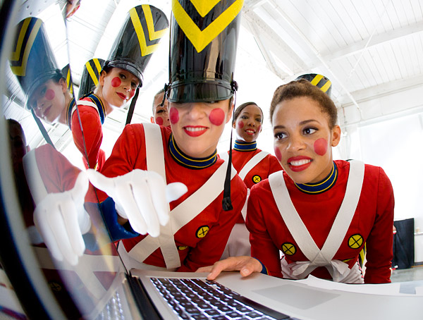 Rockettes in their toy soldier costumes check out images on a laptop at a studio photo shoot